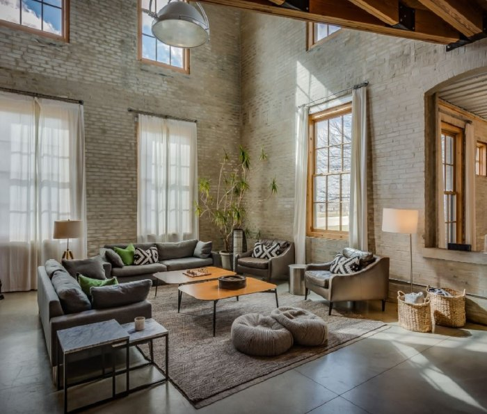A large, light-filled apartment with tall brick walls in the Journeyman Distillery.