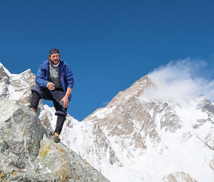 Climber posing on K2 mountain with peak in background