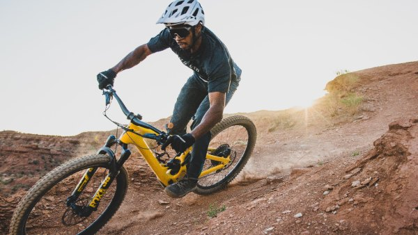 Man riding electric mountain bike over dirt trails at sunset
