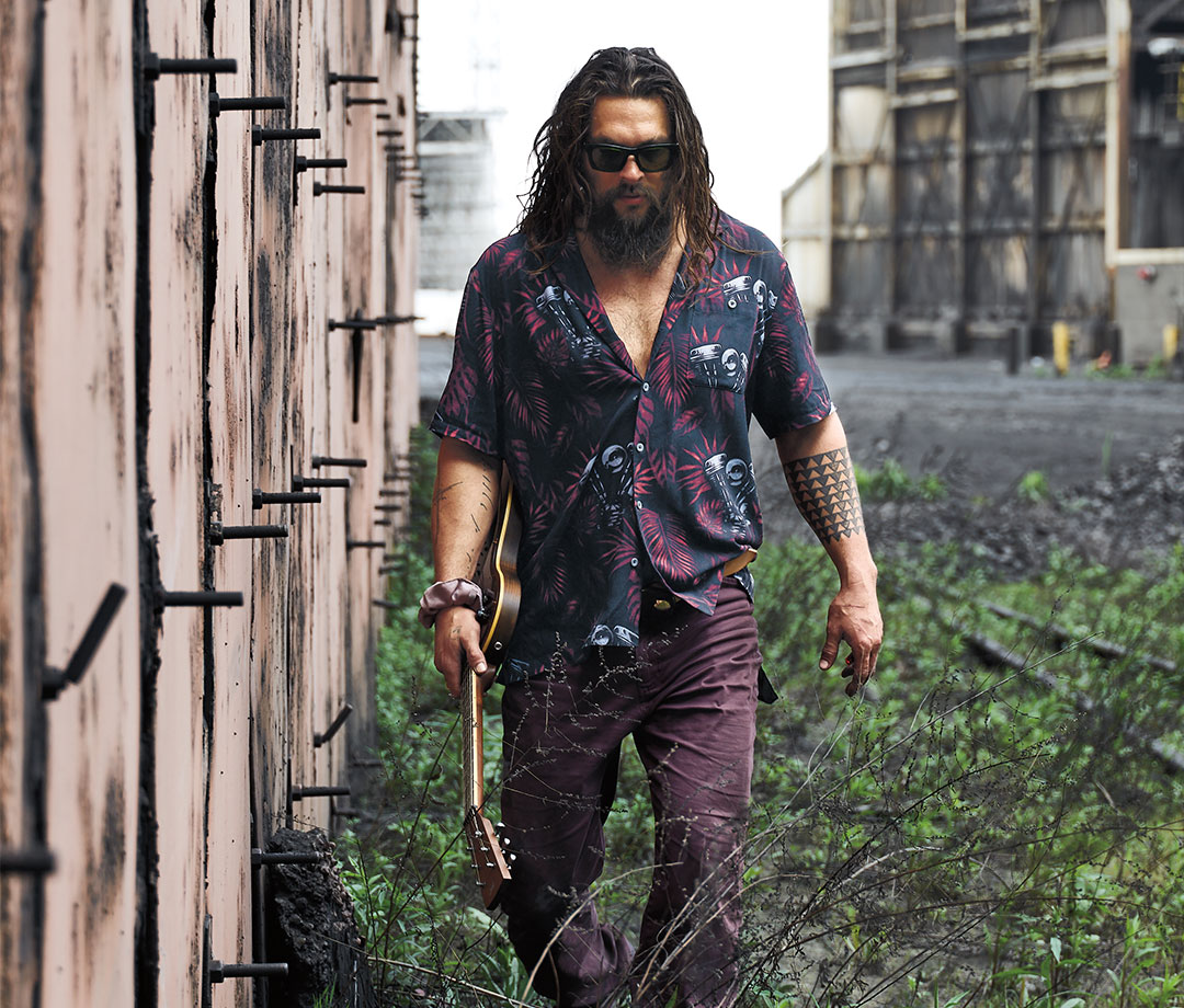 Jason Momoa walking through field with guitar in hand