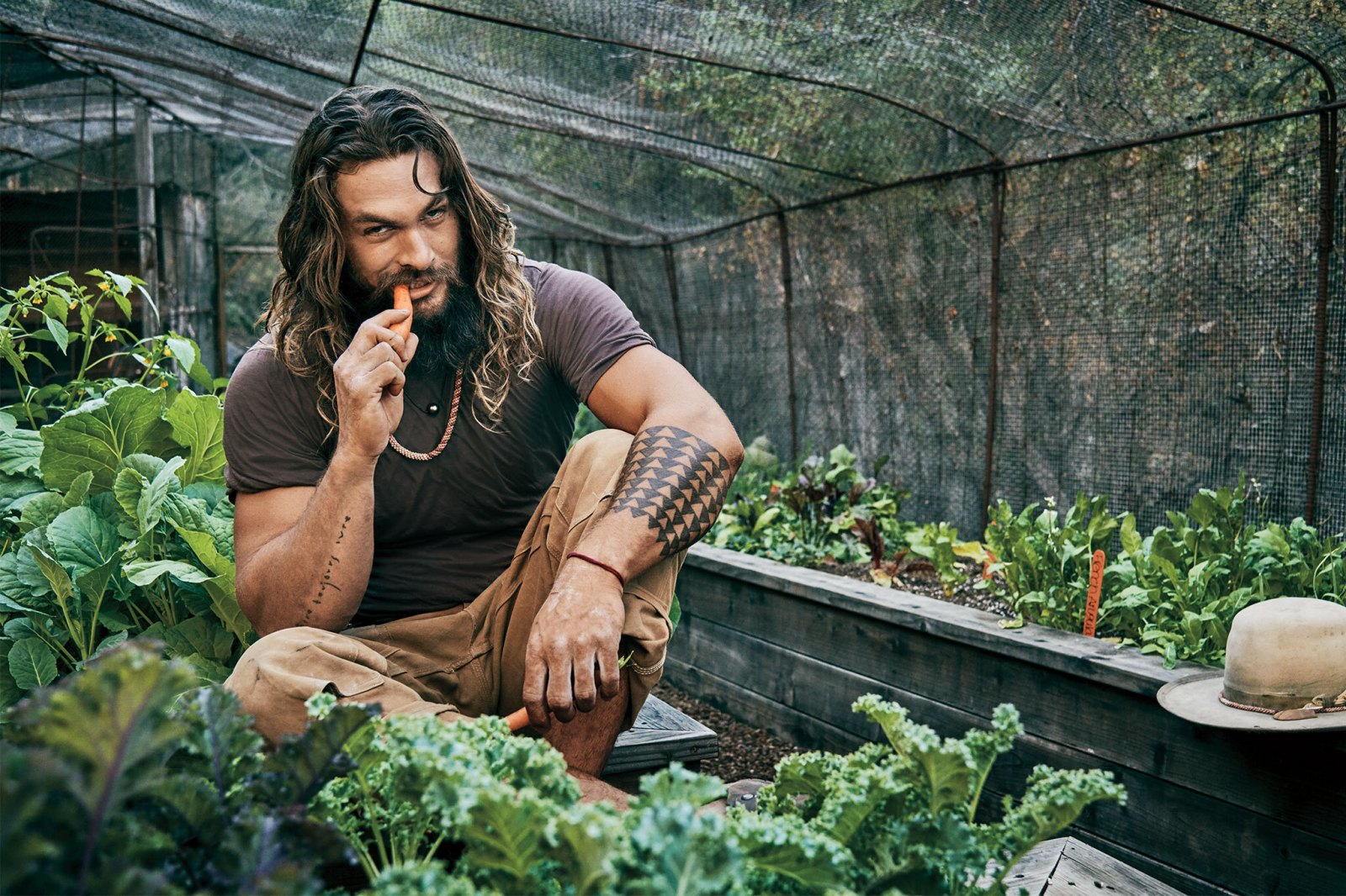 Jason Momoa eating a carrot in his home greenhouse