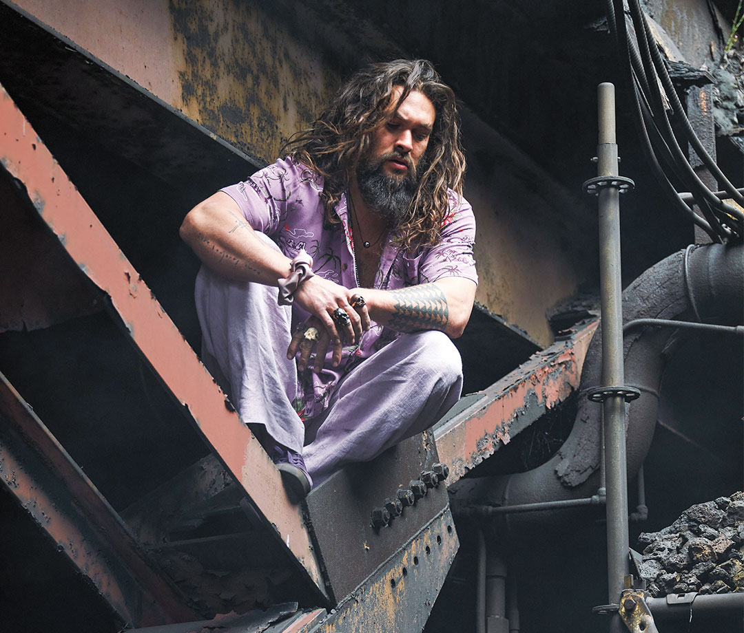 Jason Momoa perched on industrial metal