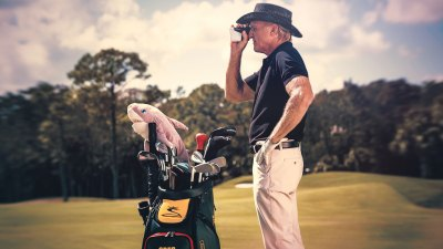 Hall of Fame golfer Greg Norman poses with golf clubs and binoculars