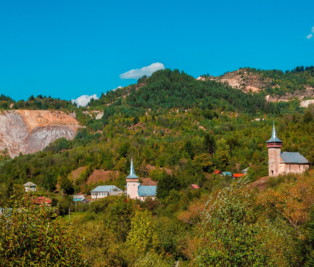 A town with Roșia Montana mines in the background.