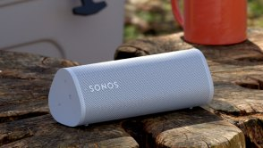 The Sonos Roam portable speaker sitting on rocks, in front of a cooler and a mug.