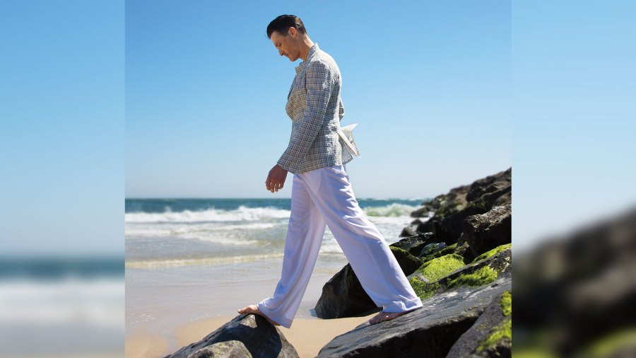 Man wearing linen pants and suit jacket on beach