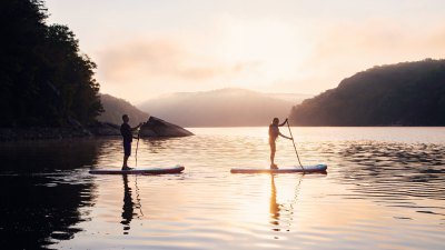 A man and a woman stand-up paddleboard in West Virginia's Summersville Lake.