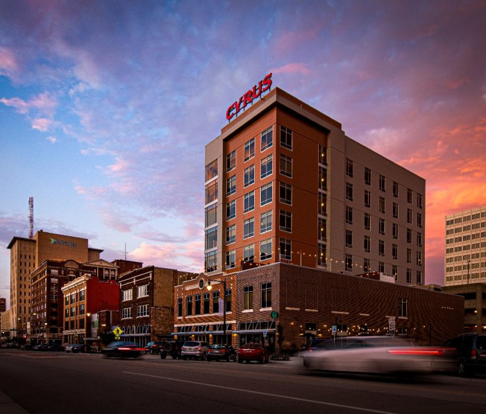 """A view of a street in downtown Topeka, Kansas. The tallest building has a sign that says """"Cyrus""""."""