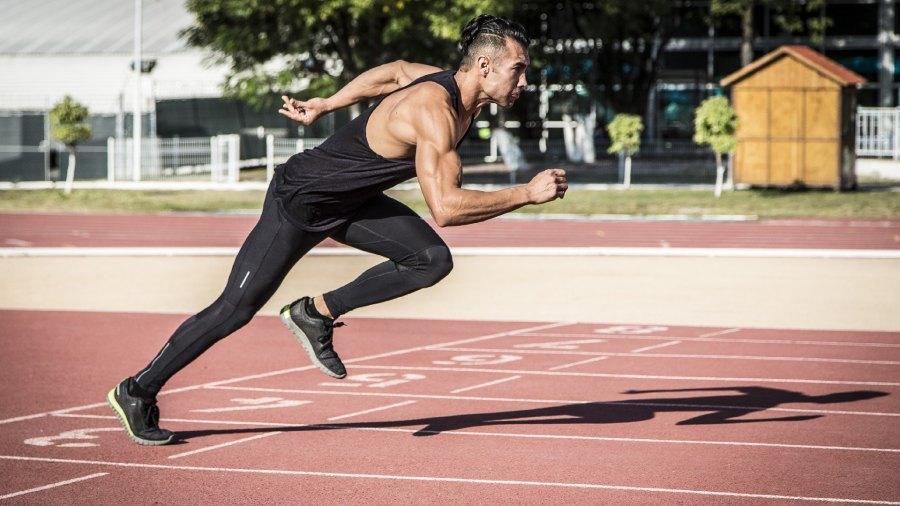 A man in workout gear sprints on an outdoor track.