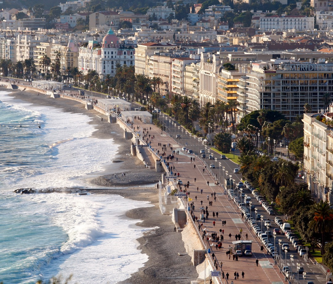 An aerial shot of Nice, France with the sea, beach, and city buildings.