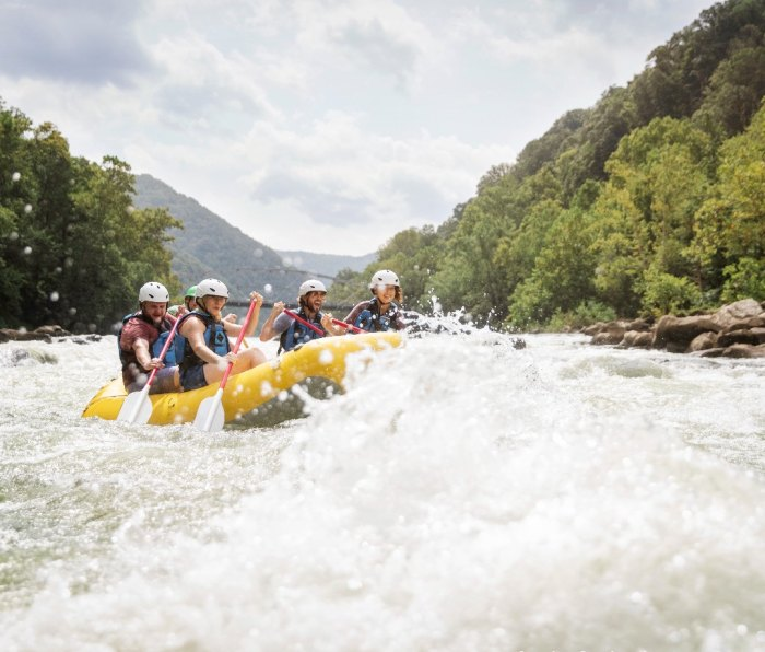 A raft with paddlers goes through whitewater in West Virginia's New River Gorge.