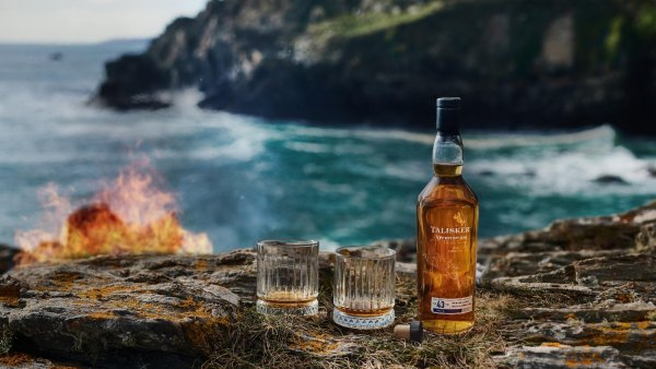 A bottle of Talisker scotch and two glasses in front. In the background, the rocky Scottish coast, the ocean, and fire.