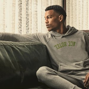 Black man sitting on couch wearing sweatshirt from Hiro Clark x Ace Hotel collaboration