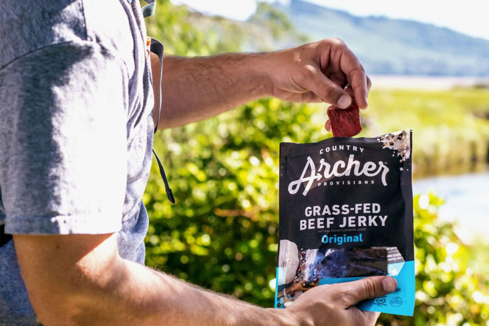 Man eating Country Archer Grass-Fed Beef Jerky in outdoors