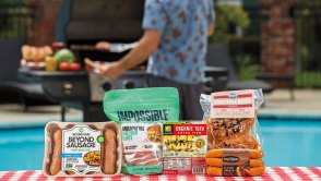 Vegan BBQ products on picnic table with man grilling in background