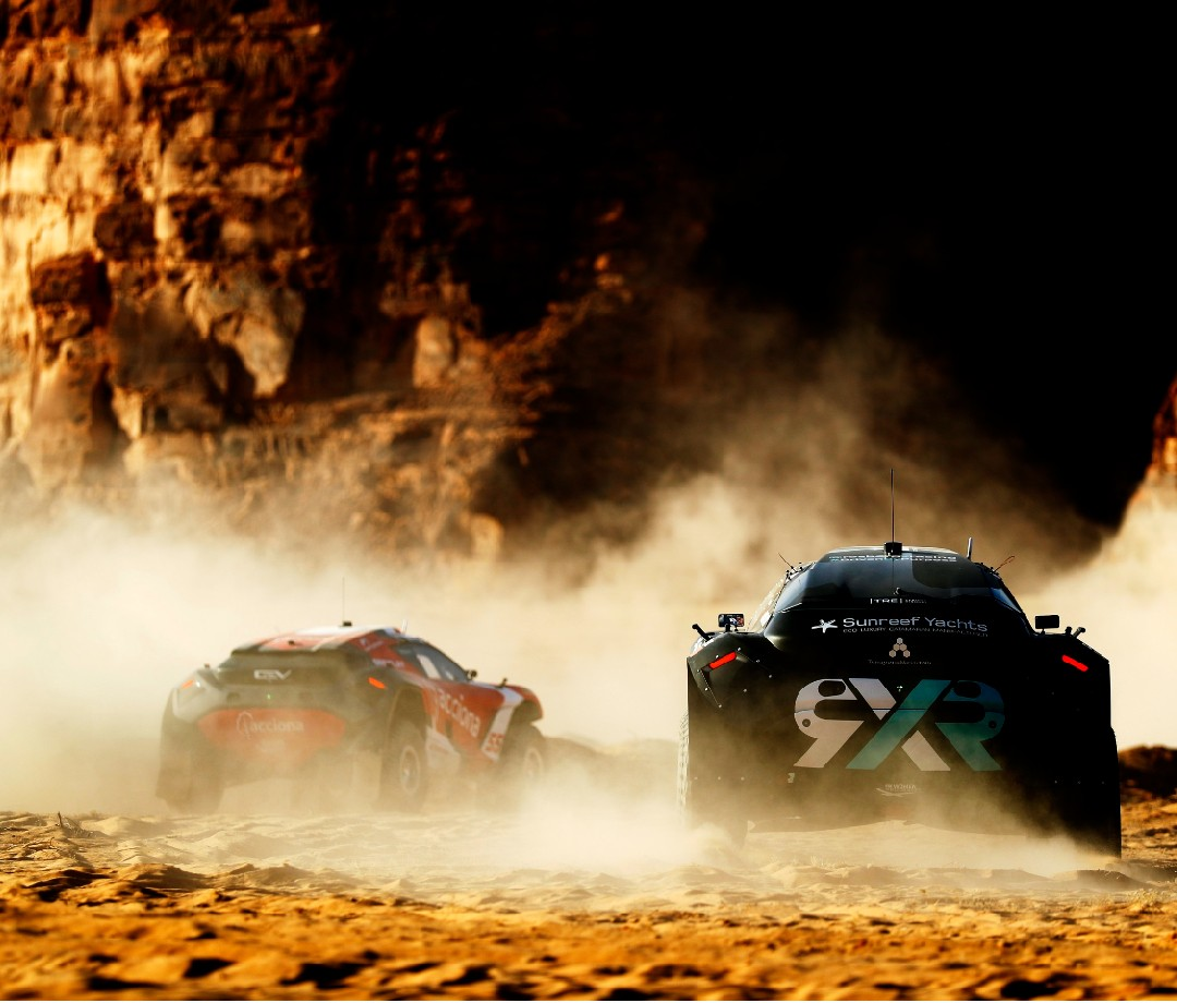 Extreme-E off-road SUVs racing in desert.