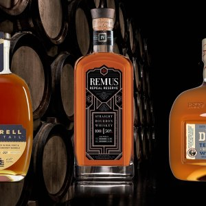 Barrell Dovetail, Remus Repeal Reserve, and George Dickel 15-Year-Old Single Barrel bourbon bottles on top of barrels