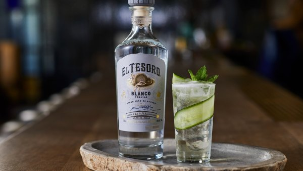 Bottle of El Tesoro Blanco tequila next to cocktail