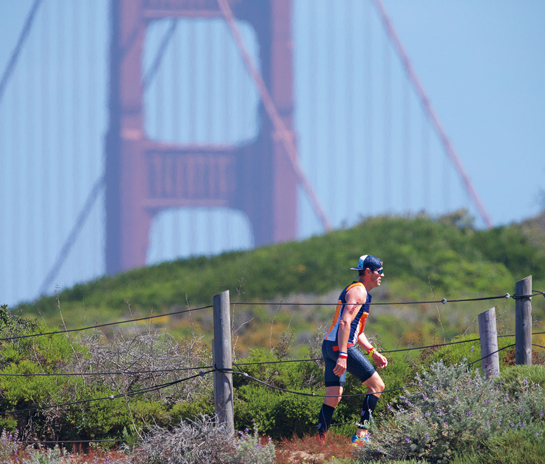 Runner walking up Sand Ladder with San Francisco Bridge in the background.