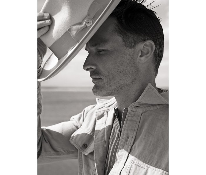 Black and white portrait of man putting hat on with ocean in background