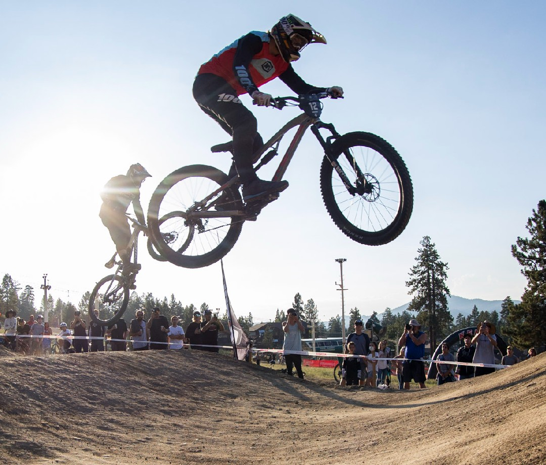 Two bike racers jump high above the course.