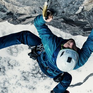 Ice climber hanging on by poles