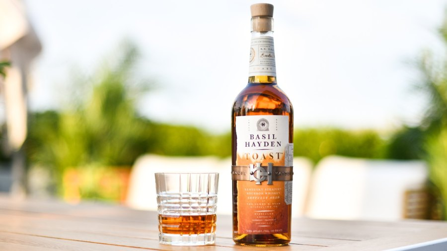 A bottle of Basil Hayden Toast and a glass with bourbon in it.