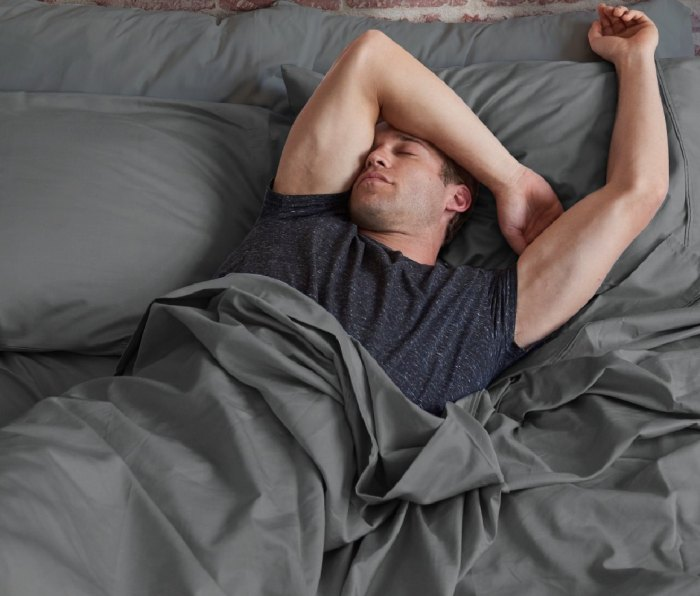 A man in a bed with Celliant Performance Sheets from Sleepletics.