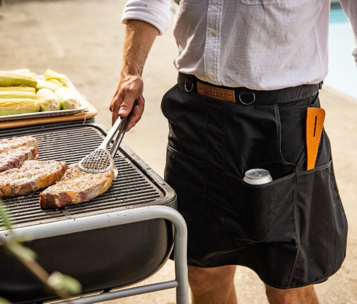 A man grilling while wearing a grillkilt.