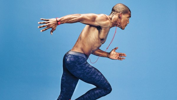 Shirtless man running with headphones against blue backdrop