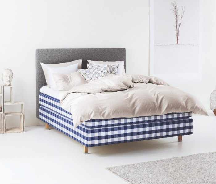 A image of a blue plaid Hästens Herlewing mattress in a bedroom.