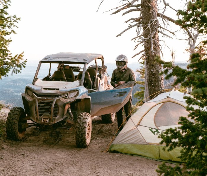 UTV rider parked beside his tent at a mountain campsite