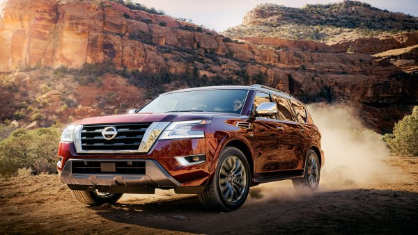 Action shot of 2021 Nissan Armada on a dirt road with desert mountains in the background