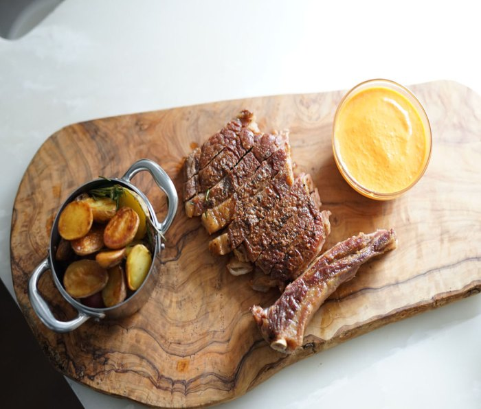 Ribeye laid out on a wooden platter with a dipping sauce and side dish