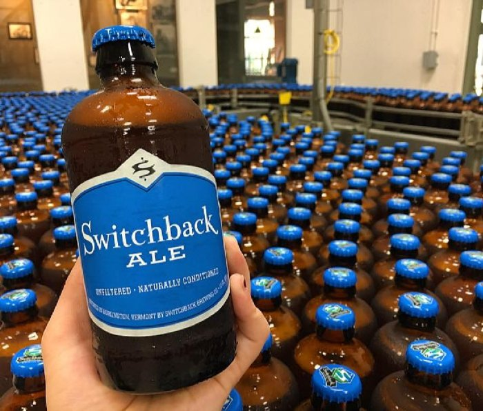 A bottle of Switchback Brewing Co. Switchback Ale in front of a bottling line featuring many more beers.