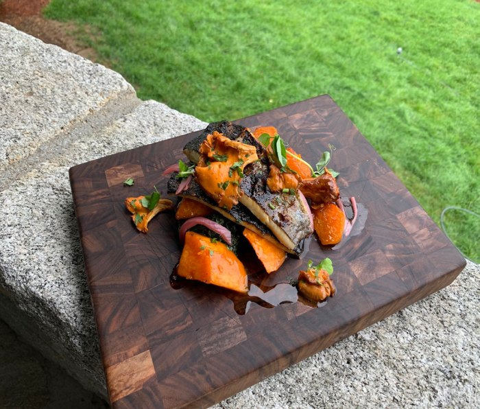Grilled Trout with Sweet Potatoes and Braised Greens on a platter sitting on a wall
