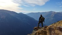 used outdoor gear man standing on top of a ridge