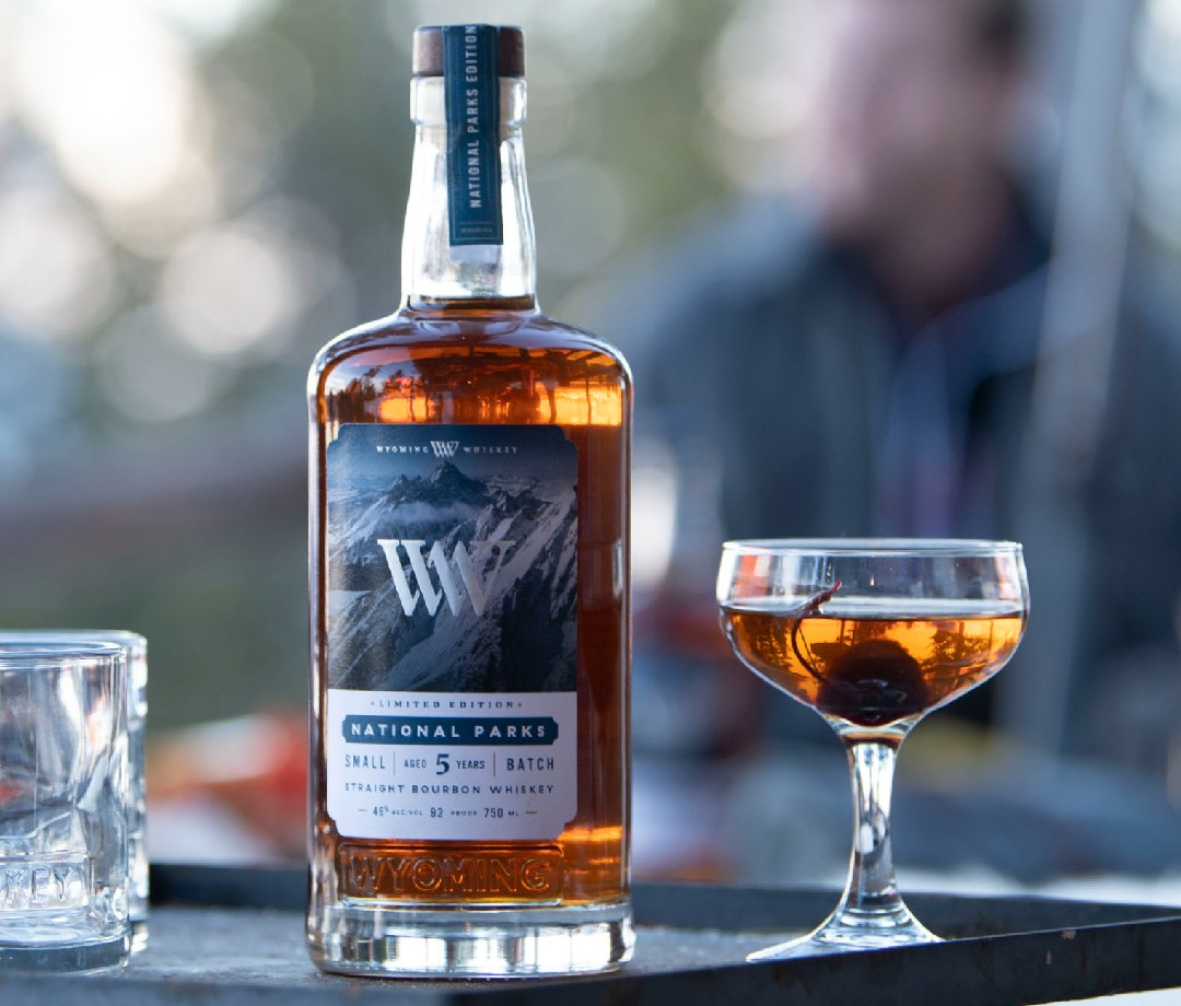 A bottle of Wyoming National Parks Limited Edition Small Batch Bourbon next to what may be an Old Fashioned cocktail.
