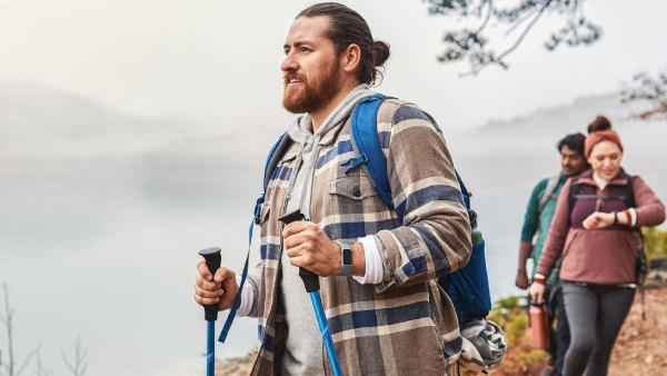 Man wearing flannel and backpack hiking outdoors