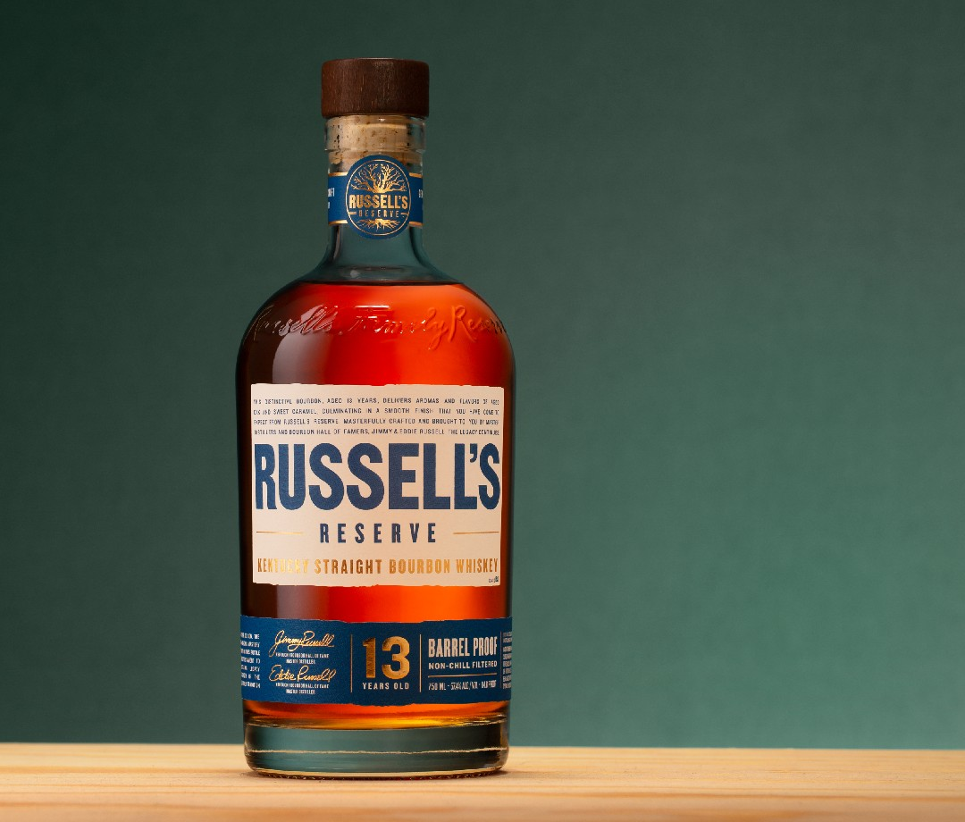 Bottle of Russell's Reserve 13-Year-Old bourbon against green backdrop