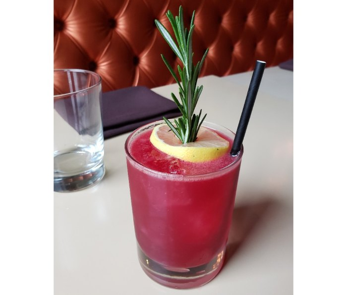 Beet cocktail with lemon and rosemary sprig as garnish