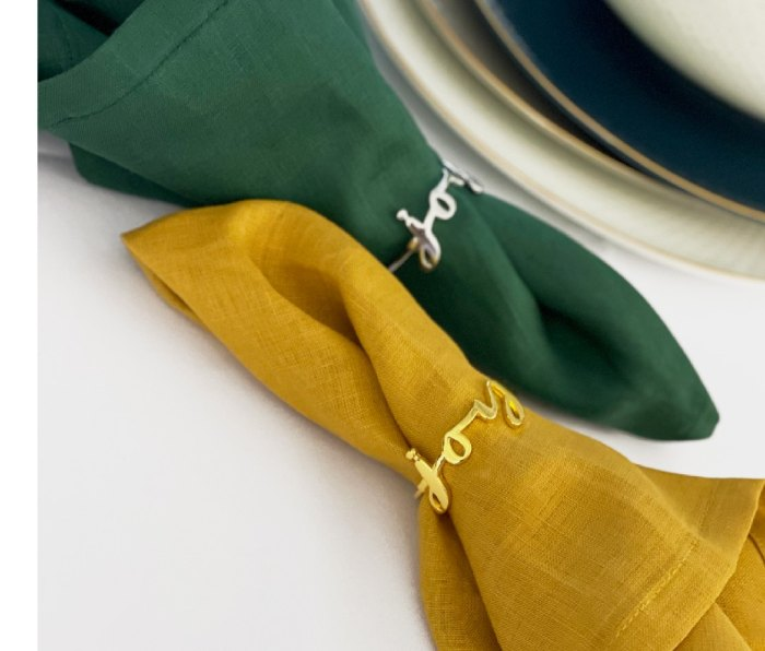 """Pair of Tea + Linen """"Joy"""" napkin rings in gold and silver with napkins on a table"""