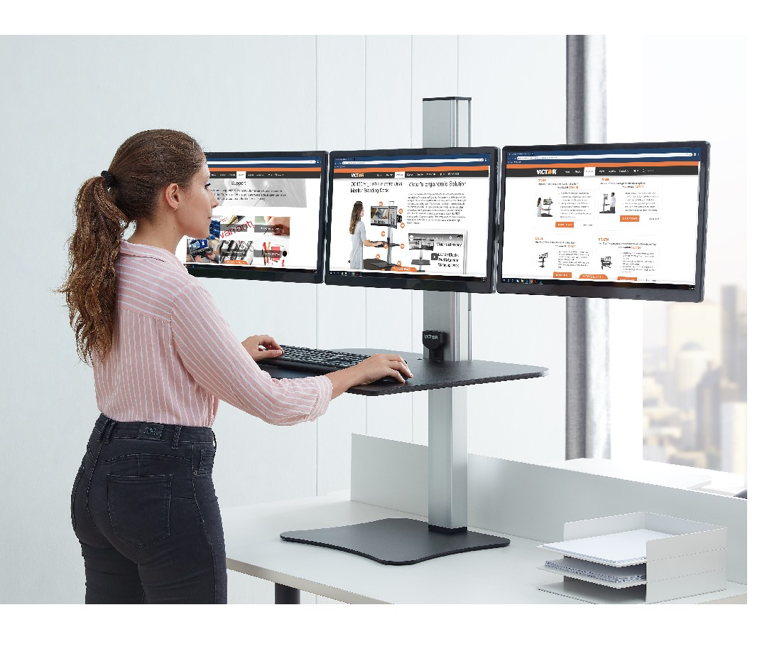 Woman standing at work on a Victor DC475 High Rise Electric Triple Monitor Standing Desk