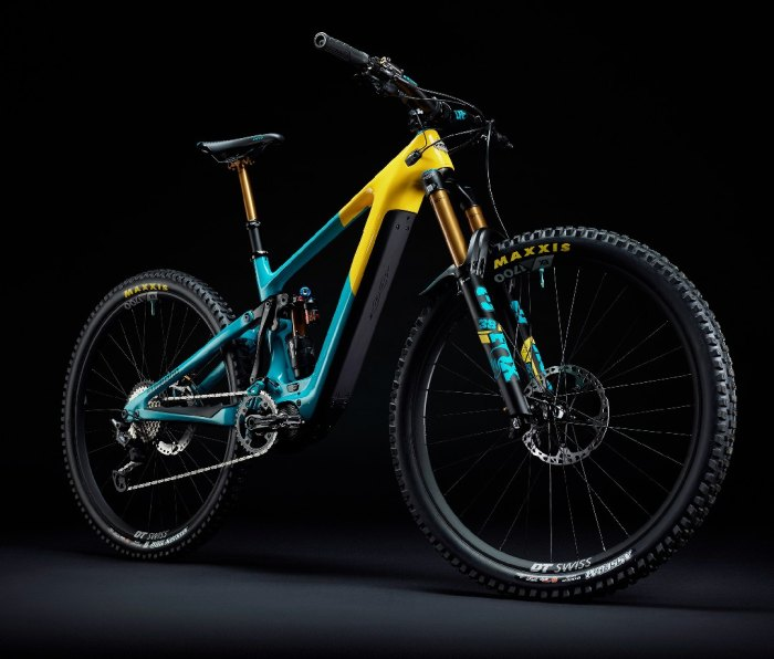 Bright blue and yellow electric mountain bike against black backdrop