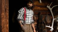 Bearded man wearing a flannel shirt and suspenders