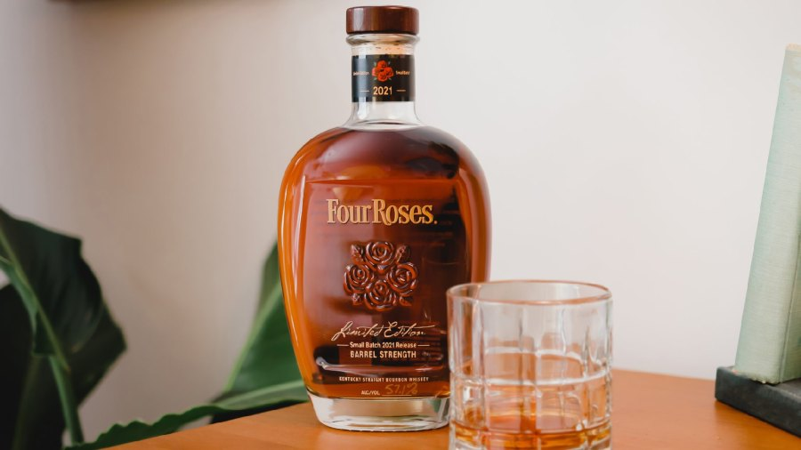 A glass next to a bottle of 2021 Four Roses Small Batch bourbon.