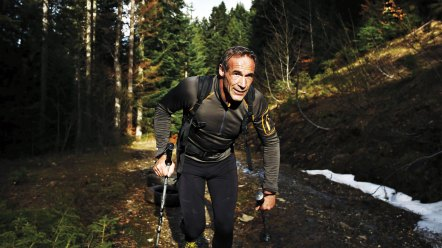 Man trekking along trail with hiking pole