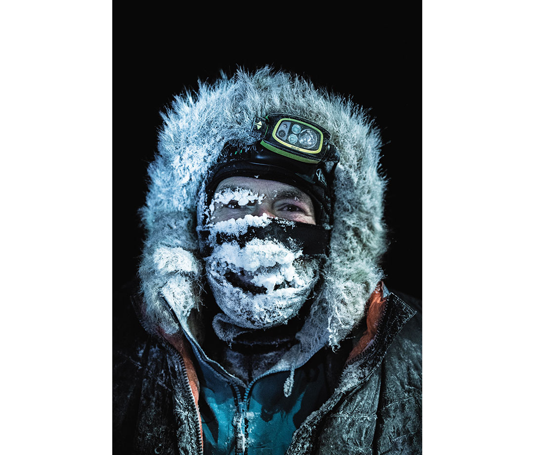 Man wearing fur hood and head lamp with frost covering face