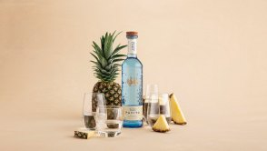 Maestro Dobel Pavito against a tan background surrounded by pineapple and glasses