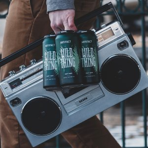 Guy carrying holding a 4-pack of Wild Thing cider and a boombox